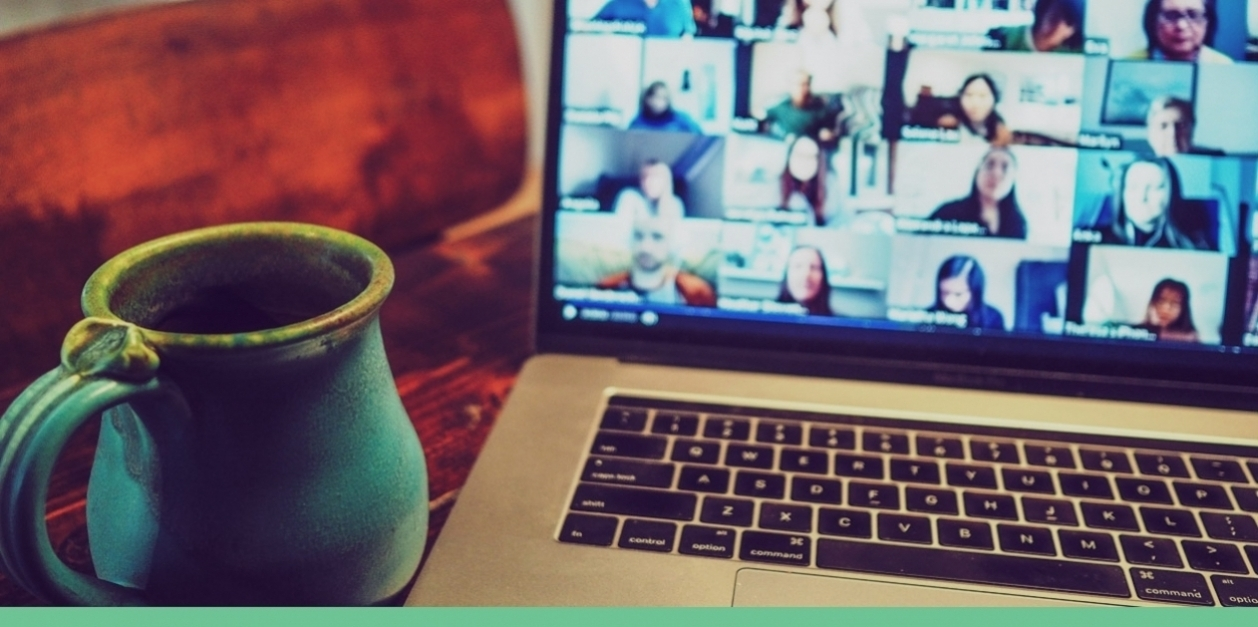 mug by computer with people on screen