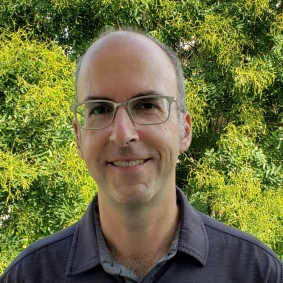 Headshot of Bob Gourley against green bush or tree wearing a blue-gray button up shirt